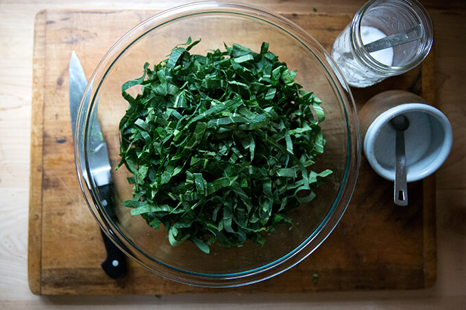 A bowl of raw, slivered collard greens aside a knife, and bowls of salt and sugar.
