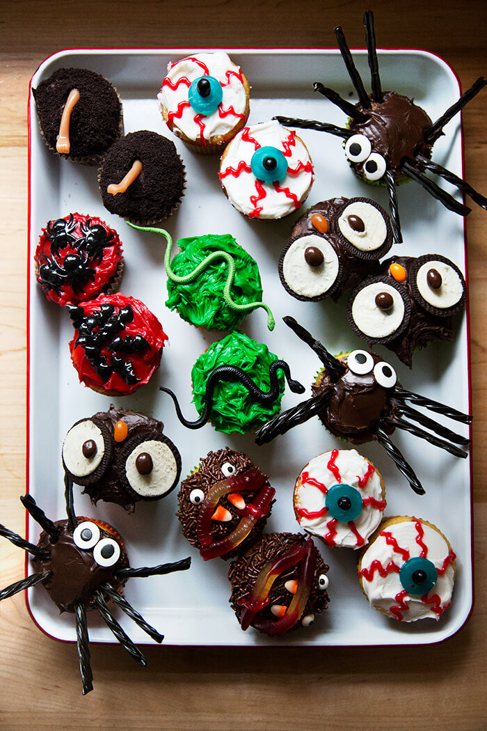 A tray filled with festively decorated Halloween cupcakes.