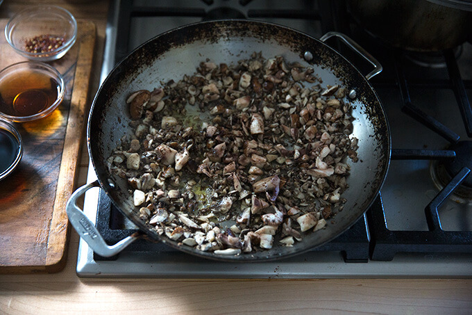 A large sauté pan filled with chopped mushrooms being sautéed in olive oil.