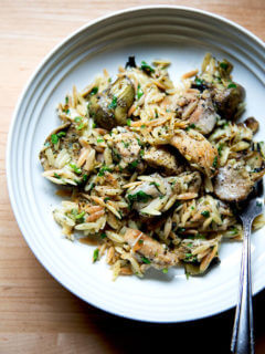 A plate of one-pan lemon chicken orzo with artichoke hearts.