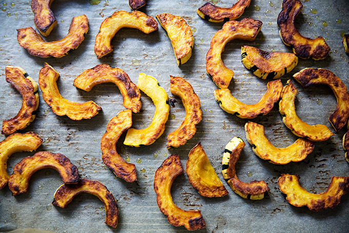 Roasted delicata squash slices on a sheet pan.