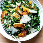 A bowl of raw collard green salad with roasted delicata squash, toasted almonds, golden raisins, and shaved parmesan.