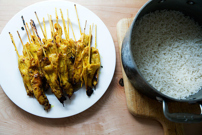 A plate of easy Thai chicken satay aside a pot of coconut rice.