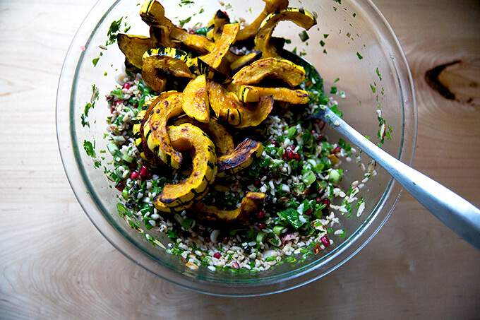 An overhead shot of a glass bowl filled winter tabbouleh and roasted delicata squash.