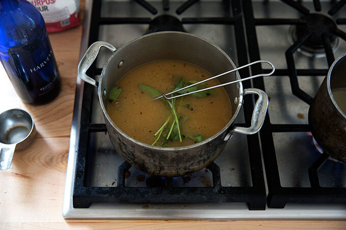 A saucepan filled with gravy simmering with sage.
