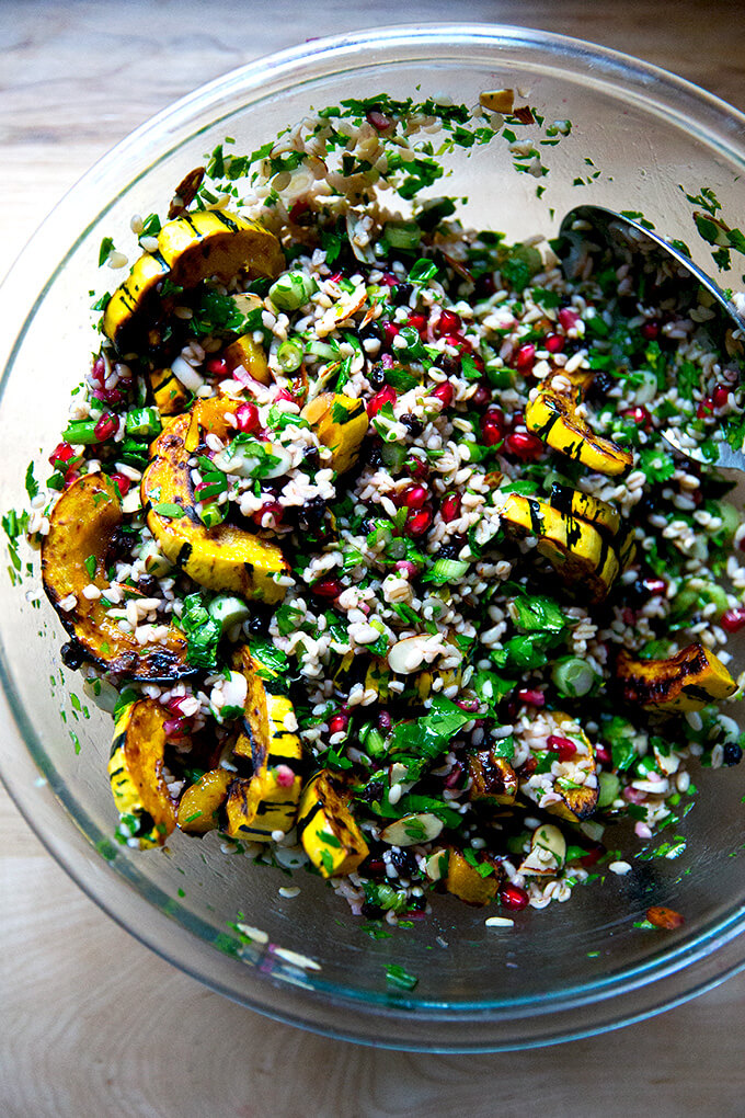 An overhead shot of a glass bowl filled winter tabbouleh and roasted delicata squash all tossed together.