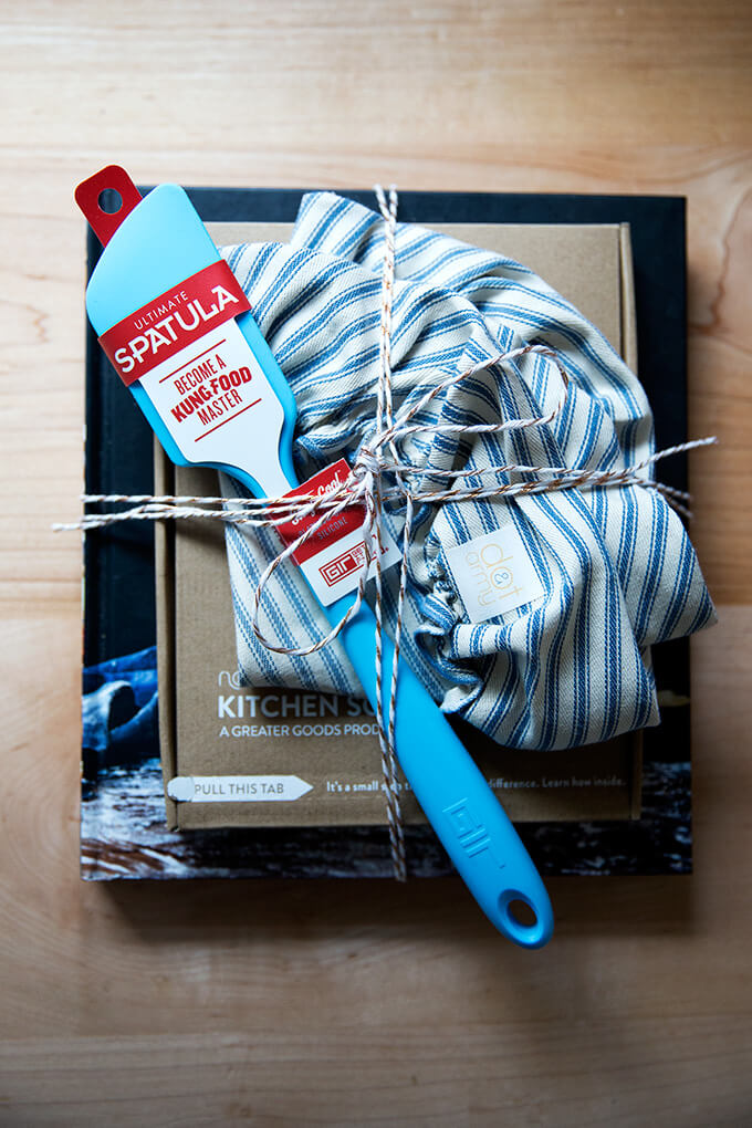 A wrapped gift set: Bread Toast Crumbs, a spatula, a cloth bowl cover, a scale, and a card.
