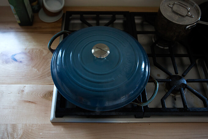 A covered Le Creuset braiser on the stovetop.