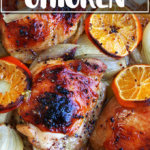 A Roasting pan filled with roast chicken and clementines.