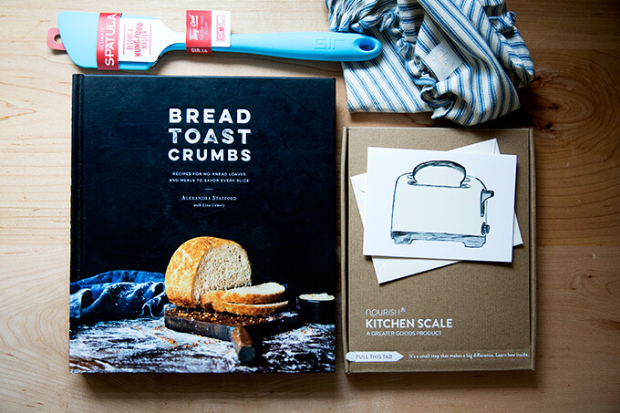 The contents of the Bread Toast Crumbs gift set: Bread Toast Crumbs, a spatula, a cloth bowl cover, a scale, and a card.