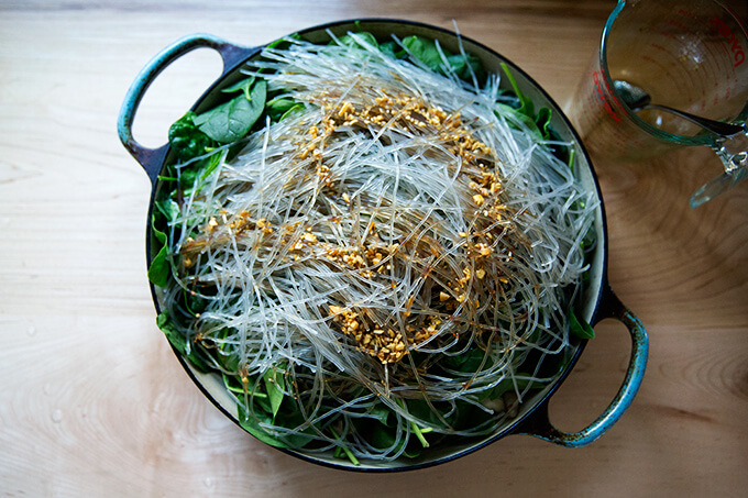 Soaked sweet potato noodles on top of spinach in a braiser.