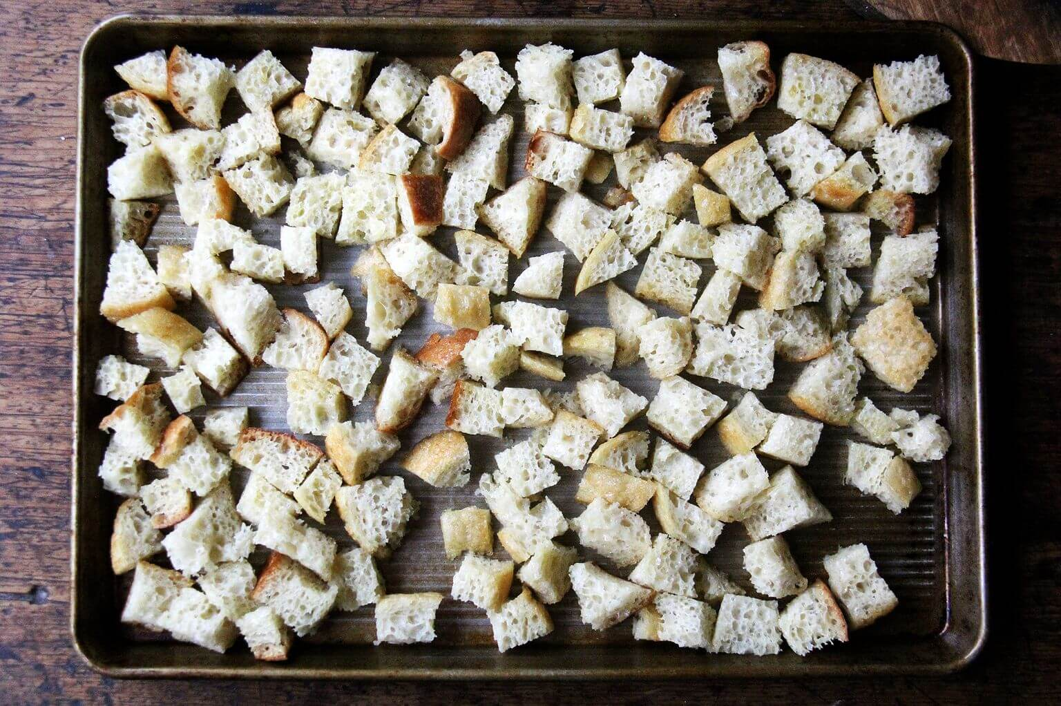 A sheet pan with cubed peasant bread tossed in olive oil.