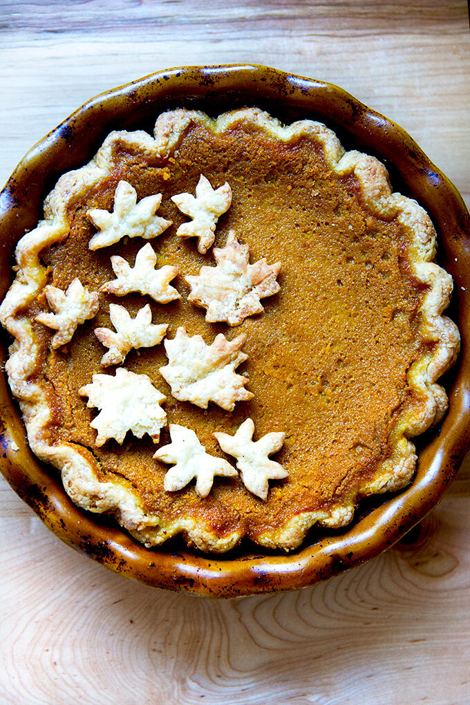A pumpkin pie decorated with pie cookies.