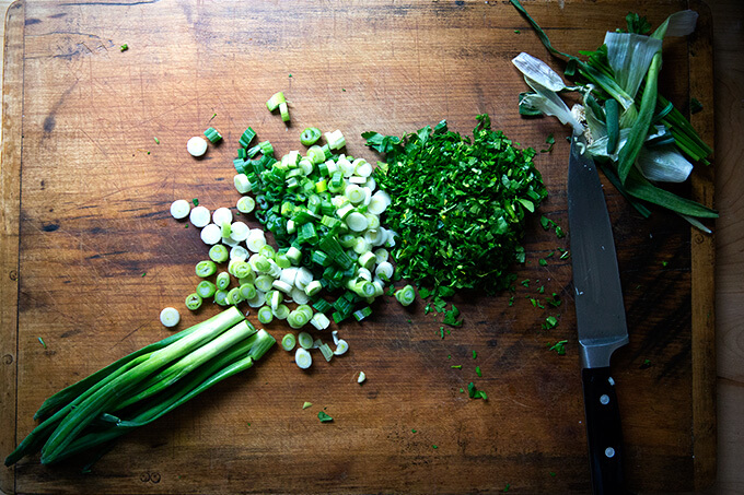 An overhead shot of a board filled with chopped scallions and parsley.