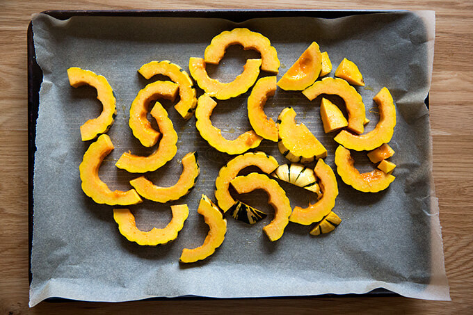 A sheet pan lined with parchment paper spread with delicata squash slices, olive oil, and salt.