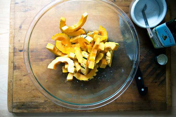 A large glass bowl filled with delicata squash slices, olive oil, and salt.