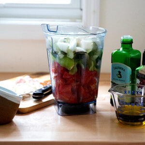 A vitamix filled with vegetables.