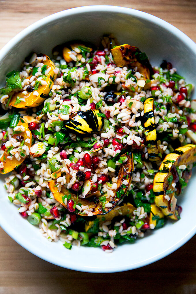 A white serving bowl filled with winter tabbouleh and roasted delicata squash slices.