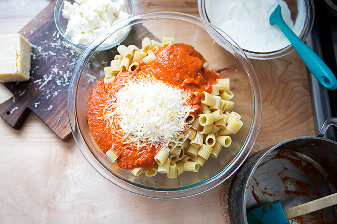 A large bowl filled with cooked pasta, vodka sauce, and parmesan.