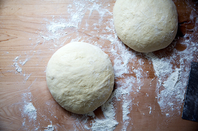 Brioche dough divided into two portions shaped into large rounds.