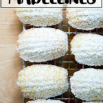 Lemon madeleines dusted in powdered sugar on a cooling rack.