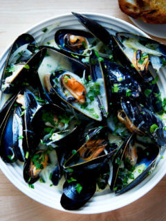 A bowl of steamed mussels aside bread.
