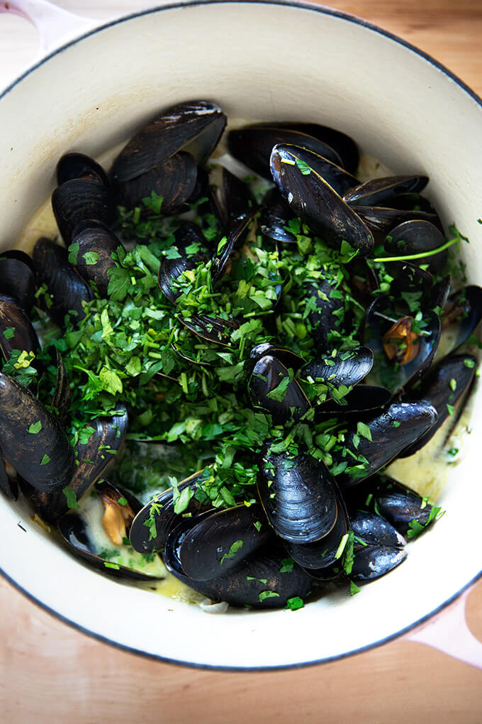 A pot of mussels, just steamed, sprinkled with parsley.