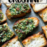Sun-dried tomato and spinach pesto spread on crostini on a sheet pan.