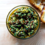 Sun-dried tomato and spinach pesto in a bowl aside bread.