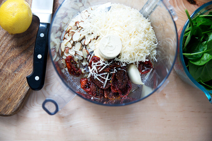 A food processor with the ingredients to make sun-dried tomato pesto.
