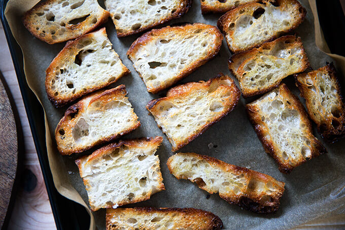 Olive oil toasted bread on a sheet pan.