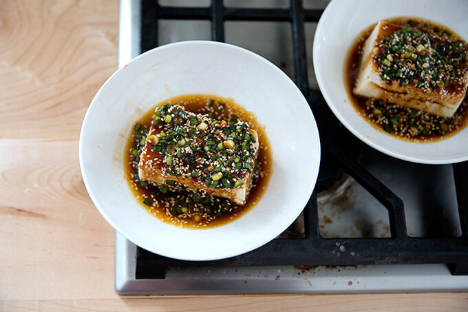 Two bowls of warm tofu topped with sesame-scallion sauce.