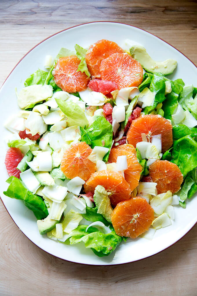 A platter topped with an endive, grapefruit and avocado salad.