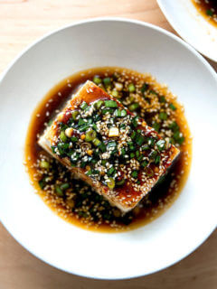 A bowl of warm tofu topped with sesame scallion sauce.