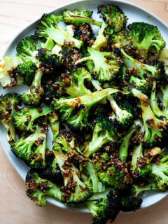 Spicy broiled broccoli with sesame-scallion oil on a plate.