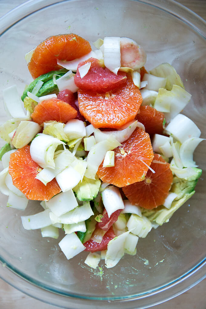 Citrus, avocado, endive in a bowl, seasoned with sea salt and tossed together.