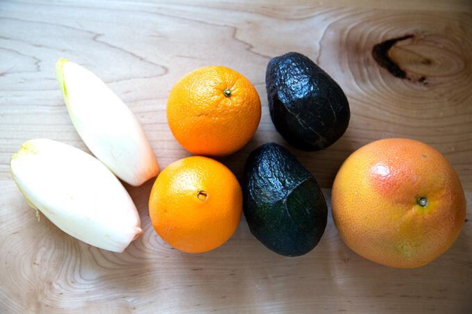Endive, Cara Cara oranges, avocados, and grapefruit on a table.