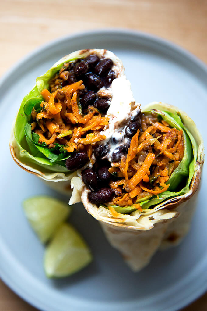 Overhead shot of halved sweet potato and black bean burrito.