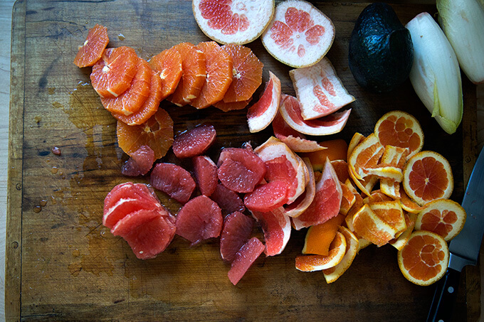 Peeled oranges and grapefruits on a cutting board.