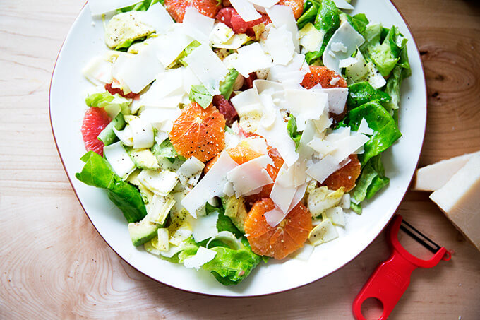 A platter topped with an endive, grapefruit and avocado salad, finished with shavings of parmesan.
