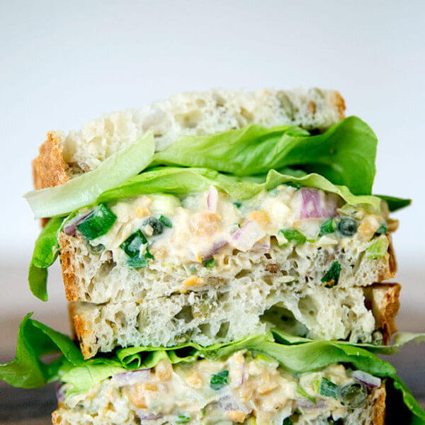 """No-tuna """"tuna"""" salad sandwich, cut and stacked on top of one another."""