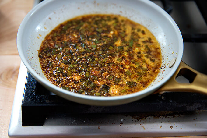 Sauce for the spicy broiled broccoli simmering in a small skillet.