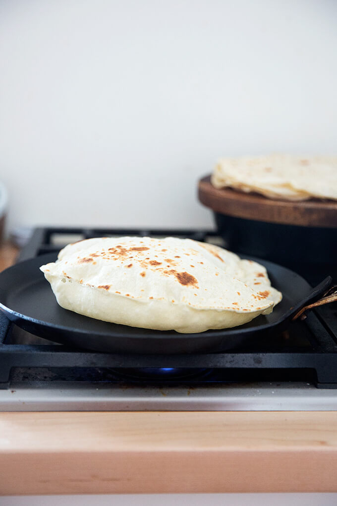 A homemade flour tortilla cooking in a skillet stovetop.