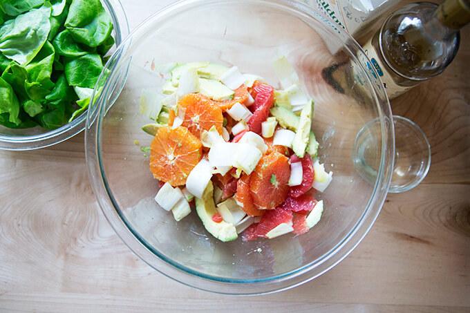 A bowl of citrus segments, avocado, endive, sea salt, and white balsamic vinegar.