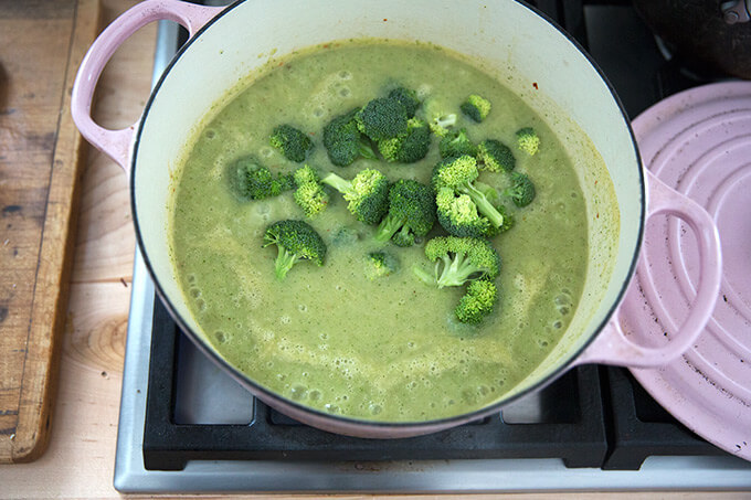A Dutch oven with puréed broccoli-cheddar soup and fresh florets added on top.