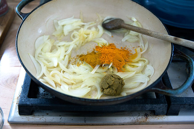 A skillet with onions, curry powder, turmeric, and Thai green curry paste.