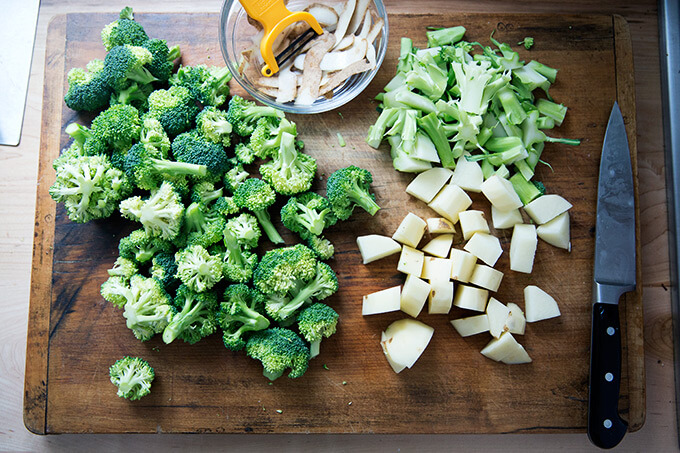 A board with broccoli florets, cubed potatoes, and broccoli stems.