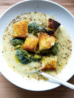 A bowl of broccoli-cheddar soup with olive oil toasted croutons and a spoon.