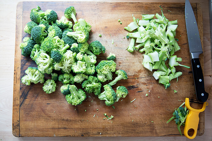 An overhead shot of a cutting board with broccoli florets and stems.