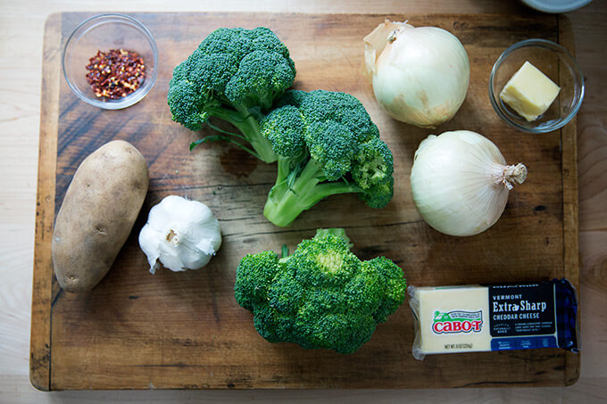 Ingredients on a board to make broccoli-cheddar soup.